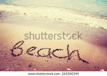 """Beach"" written on the sand / Summer holidays background - stock photo"