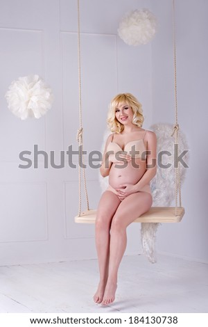 Beautiful angelic pregnant woman. Angel - stock photo