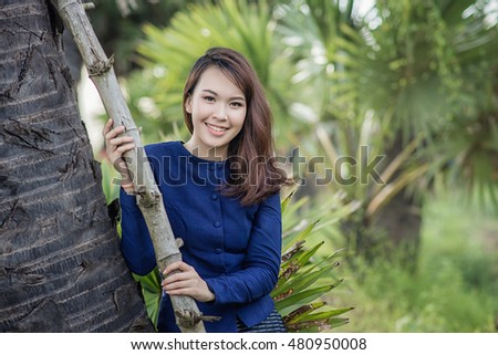 Beautiful Asian Farmer woman wearing typical Thai dress, on Rice fields background, identity culture of Thailand