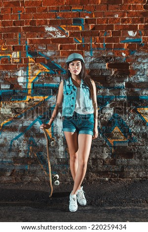 Beautiful asian teen girl with skate board. Outdoors, urban lifestyle. - stock photo