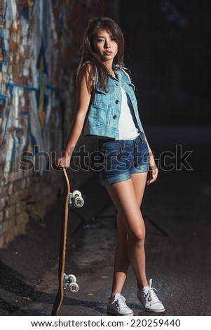 Beautiful asian teen girl with skate board. Outdoors, urban lifestyle.