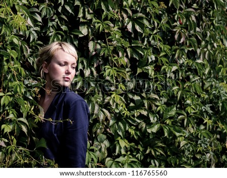 Beautiful  blonde caucasian young woman standing near the shrub and looks into the distance