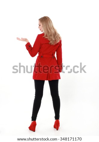 beautiful blonde young woman with blonde hair, wearing long red winter trench coat. full length standing portrait back view,  facing away from camera, hand reaching out isolated on white background. - stock photo