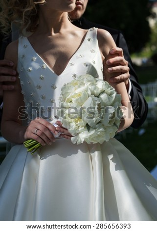 beautiful bride in a white dress holding a bouquet of wedding flowers.