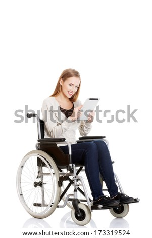 Beautiful casual woman sitting on w wheelchair with tablet. Isolated on white. - stock photo