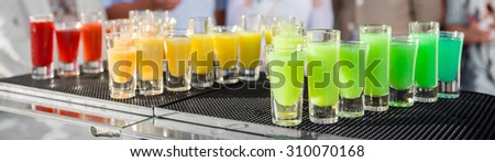 Beautiful cocktail glasses defocused on buffet table in restaurant and blurred background - stock photo