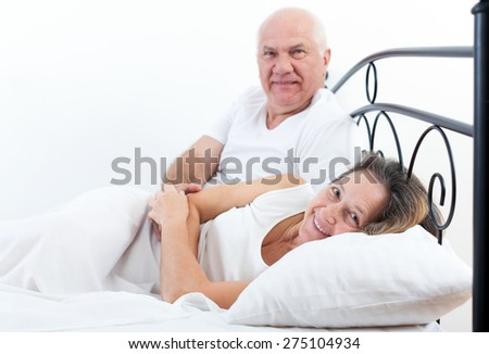 Beautiful elderly couple embracing in bed.  - stock photo