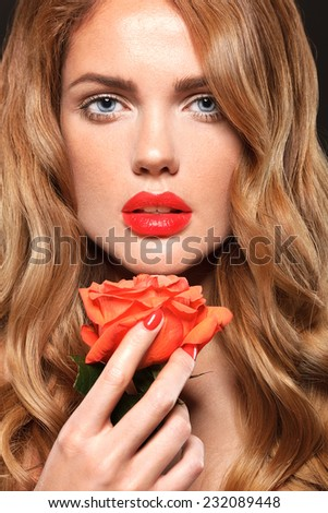 Beautiful face of a glamour woman with smoky eyes make up. Black background. Flower - stock photo