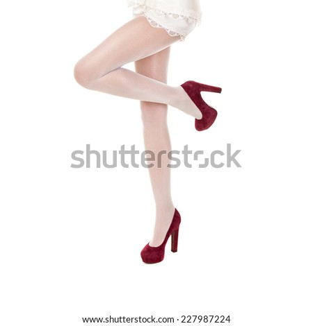 Beautiful female legs in stockings on high heels isolated on white background  - stock photo