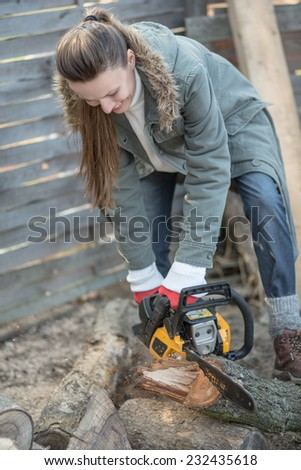 Beautiful female woodworker with chainsaw. daylight, focus on face - stock photo