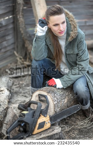 Beautiful female woodworker with chainsaw. focus on woman, daylight - stock photo