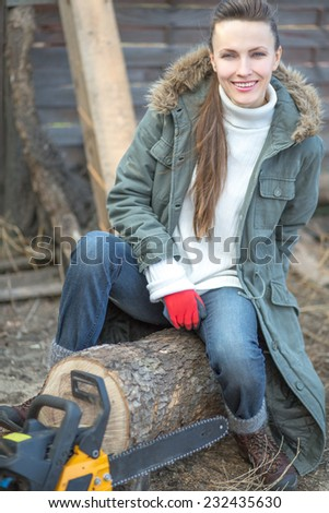 Beautiful female woodworker with chainsaw outdoors. focus on woman - stock photo