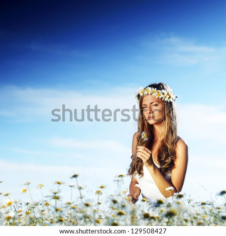 beautiful girl  in dress on the sunny daisy flowers field