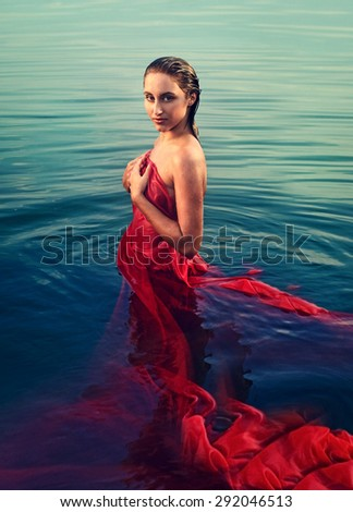 beautiful girl in red clothes posing in the water at sunset