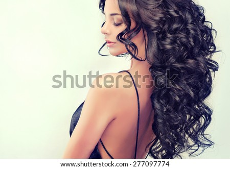 Beautiful girl model with long black  curled hair - stock photo