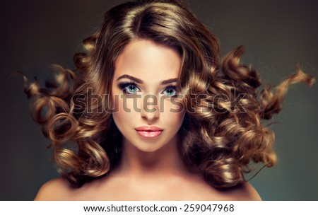 Beautiful girl model with long brown curled hair - stock photo