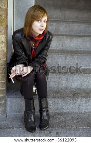 Beautiful girl sits on a stairs