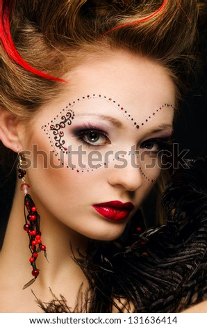 Beautiful girl with a mask and make up on gray background