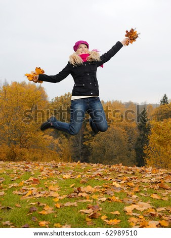 beautiful girl with autumn leafs in a park jumping and smiling - stock photo
