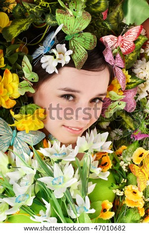 Beautiful girl with butterfly and flower on grass. Outdoor.