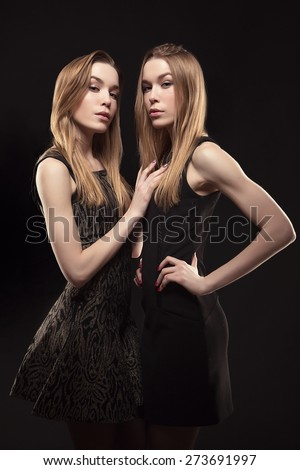 2 beautiful girls twins in the studio. fashion, seduction. Two beautiful sexy tanned girls with long hair