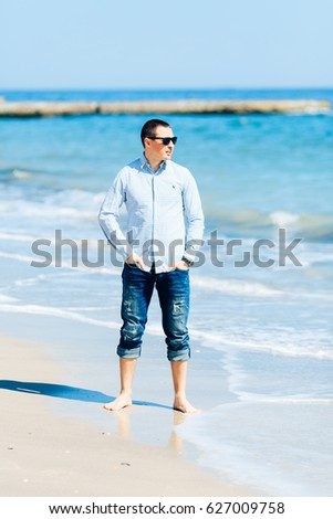 Beautiful  guy with glasses on the beach