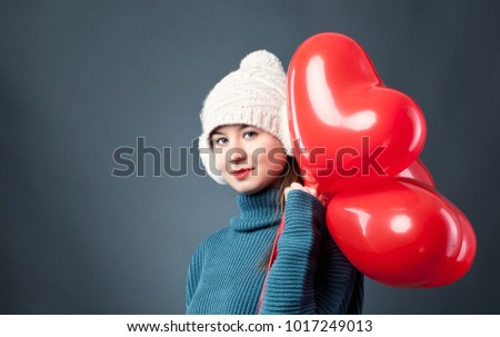 Beautiful Happy Young woman with heart shaped air baloons. holiday party. Joyful model posing, having fun, celebrating Valentine's Day