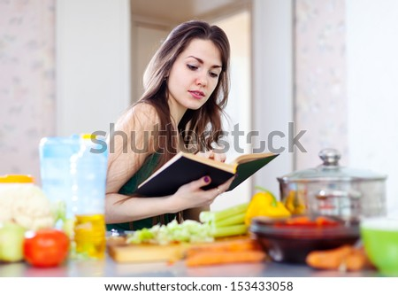beautiful housewife cooking with cookbook in  kitchen  at home - stock photo