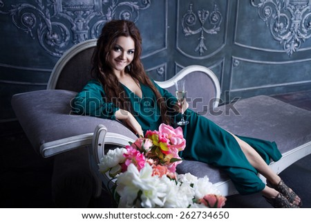 beautiful luxurious woman with a glass of champagne sitting on  vintage couch - stock photo