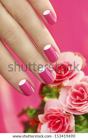 Beautiful manicures on short nails woman with a flower on a pink background. - stock photo