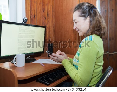 beautiful middle-aged woman near home computer   - stock photo