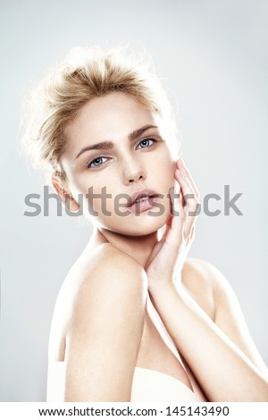 beautiful model with natural make-up, shooted on blue background - stock photo