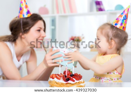 beautiful mother and her little daughter are celebrating a birthday. on the table is a cake with candles. focus on the cake. mom gives daughter gift - stock photo