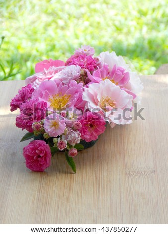 Beautiful pink rose flower bouquet blooming on wooden background