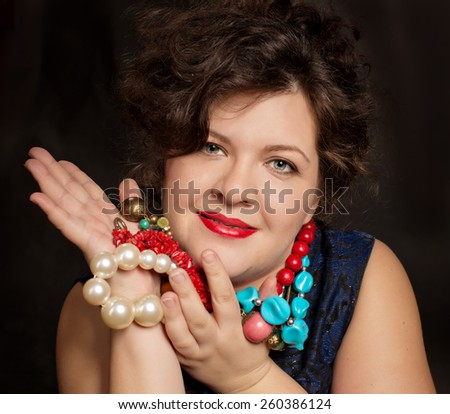 beautiful plus size  brunette  woman  playing with colorful beads over dark background  - stock photo