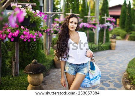 Beautiful pretty young woman walking in a park in Thailand. Pattaya. Nong Nooch Tropical Botanical Garden - stock photo