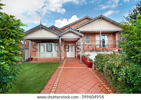 beautiful private house , red brick building. with a lawn of green grass - stock photo