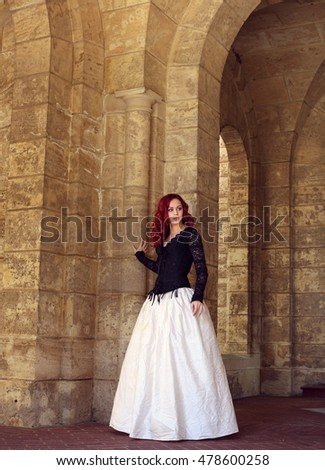 beautiful red haired woman wearing a black and white gown, wandering around a castle.