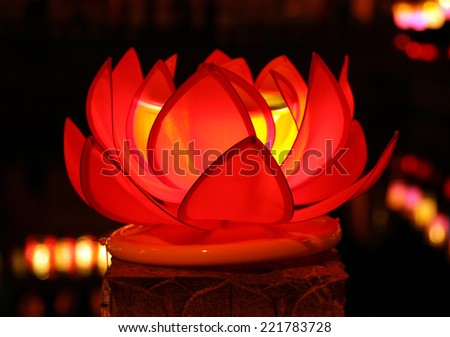 Beautiful red lotus with candle inside - traditional decoration of chinese buddhist temple, symbol of purity - stock photo