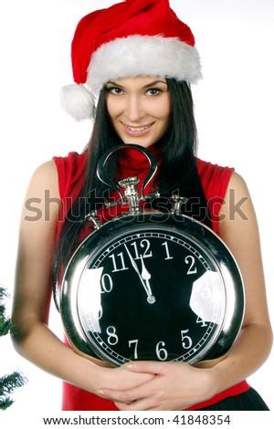 Beautiful Santa girl with clock showing midnight - stock photo