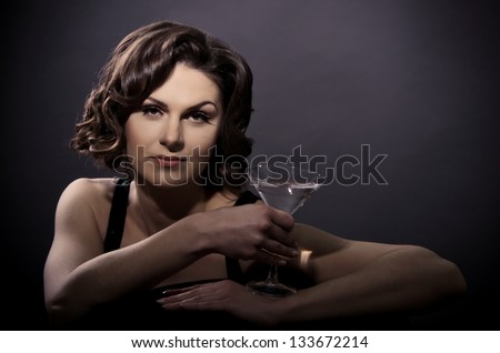 Beautiful sexy woman with a martini glass on a black background - stock photo