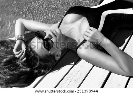 Beautiful sexy young woman with perfect slim figure with long dark hair and wet bathing suit fashion in stylish glasses from the sun is sunning by swimming pool swim, sunbathe have fun at beach party - stock photo