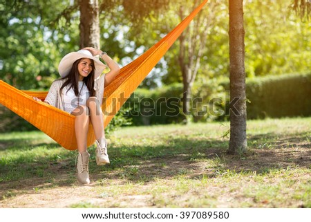 Beautiful smiling lady with big white hat sitting in hammock in forest - stock photo