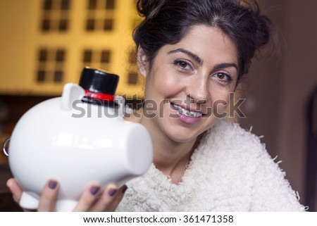 beautiful smiling woman with braces holding piggy bank - stock photo