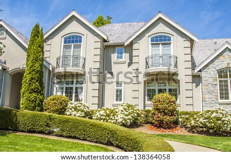 beautiful suburban luxury house at sunny day with green grass   - stock photo