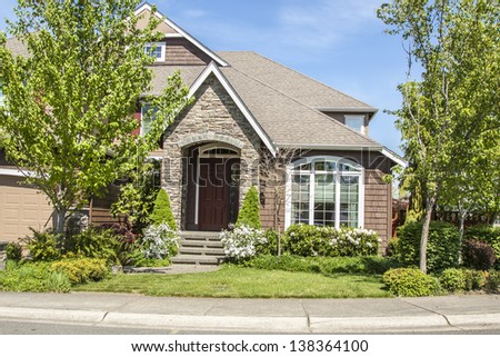 beautiful suburban luxury house at sunny day with green grass