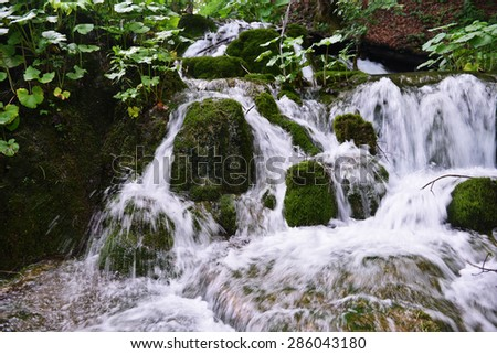 beautiful waterfalls on slopes of mountains - stock photo
