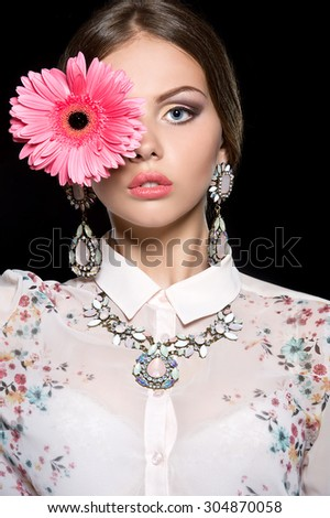 Beautiful woman face with colorful make-up and pink flower - stock photo