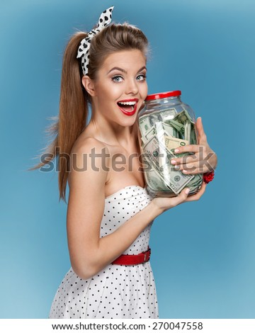 """""""Beautiful woman holding her retirement account of american dollars in a transparent bottle (jar) / photo set of young American pin-up model on blue background - stock photo"""