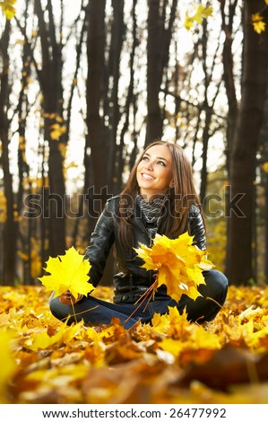 ? beautiful woman in an autumn park collects leaves